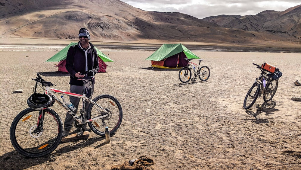 man with bicycle near tent during daytime