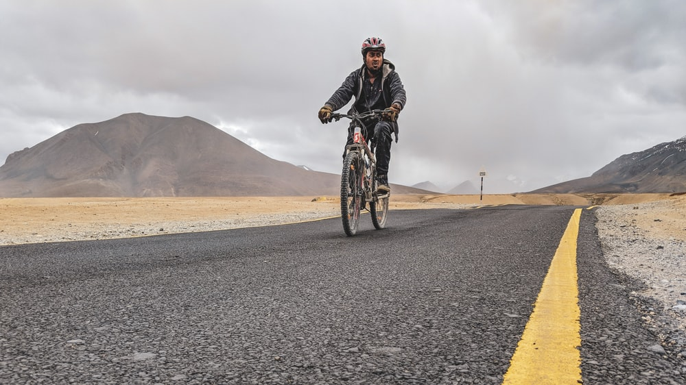 man riding bicycle on asphalt road during daytime