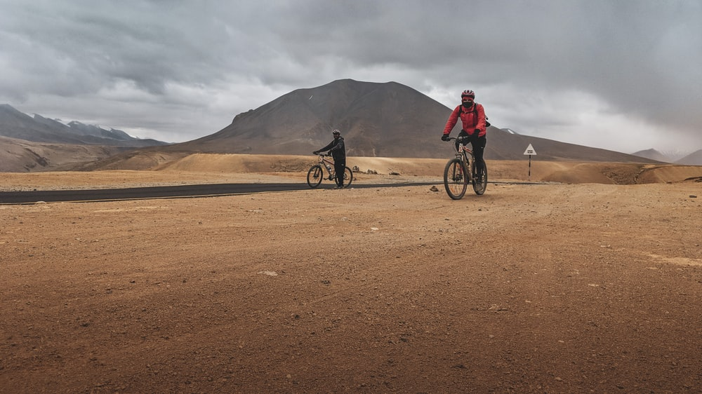 two men riding bicycle on dirt track during daytime