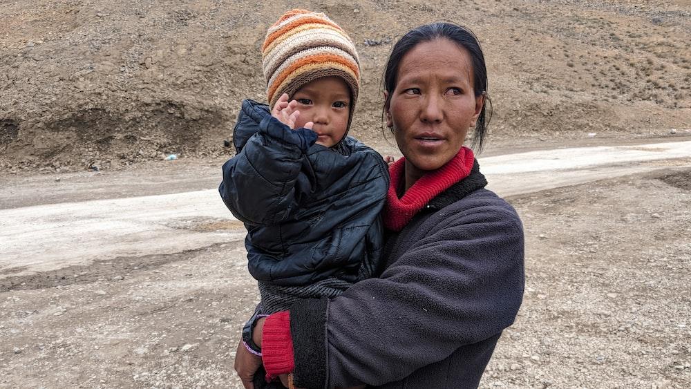woman carrying boy beside road