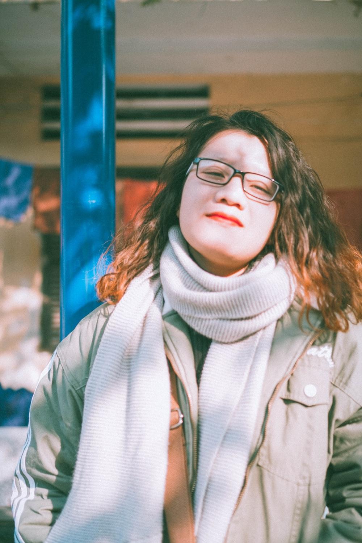 smiling woman wearing black framed eyeglasses standing outdoor during daytime