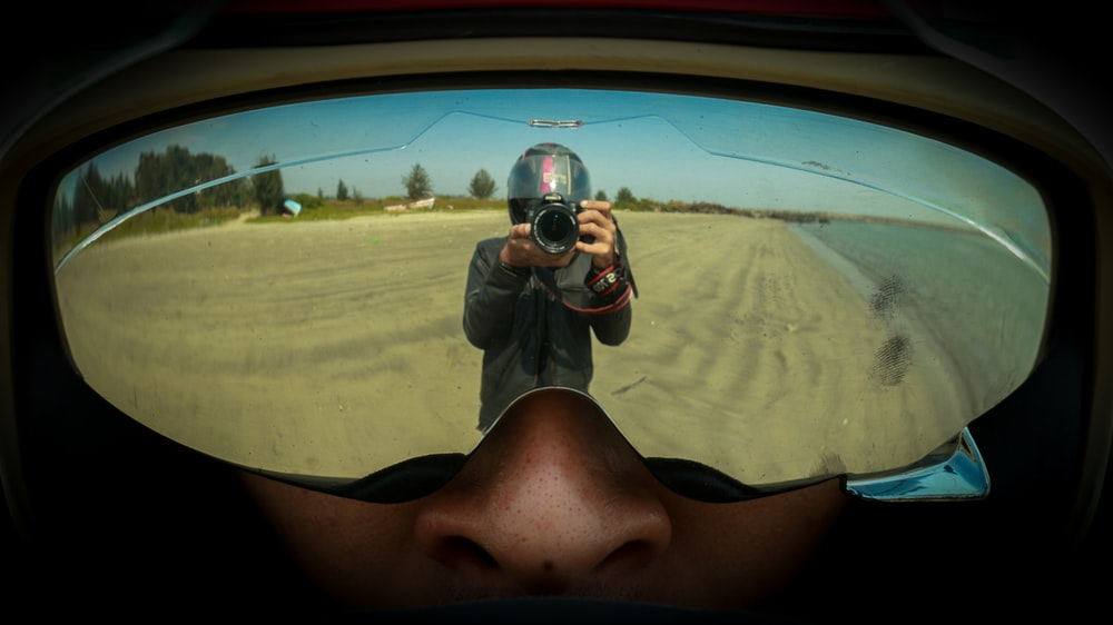 reflection photography of person holding DSLR camera
