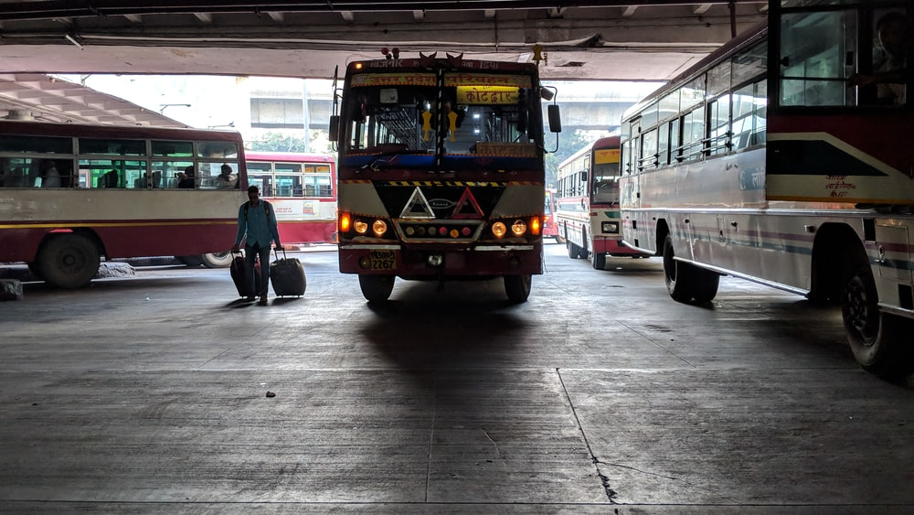 person standing in bus terminal during daytime