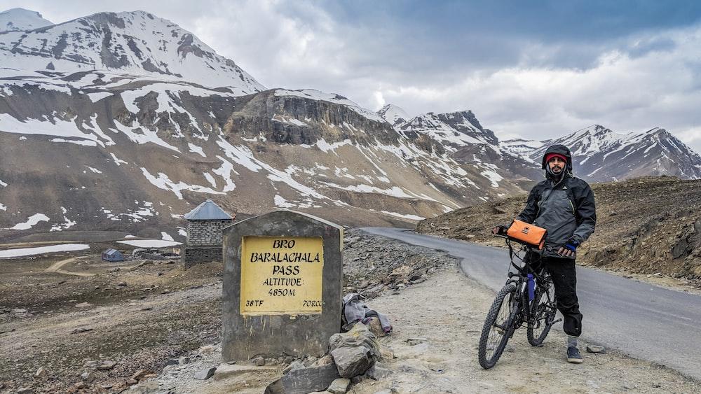 man riding on bicycle near mountain