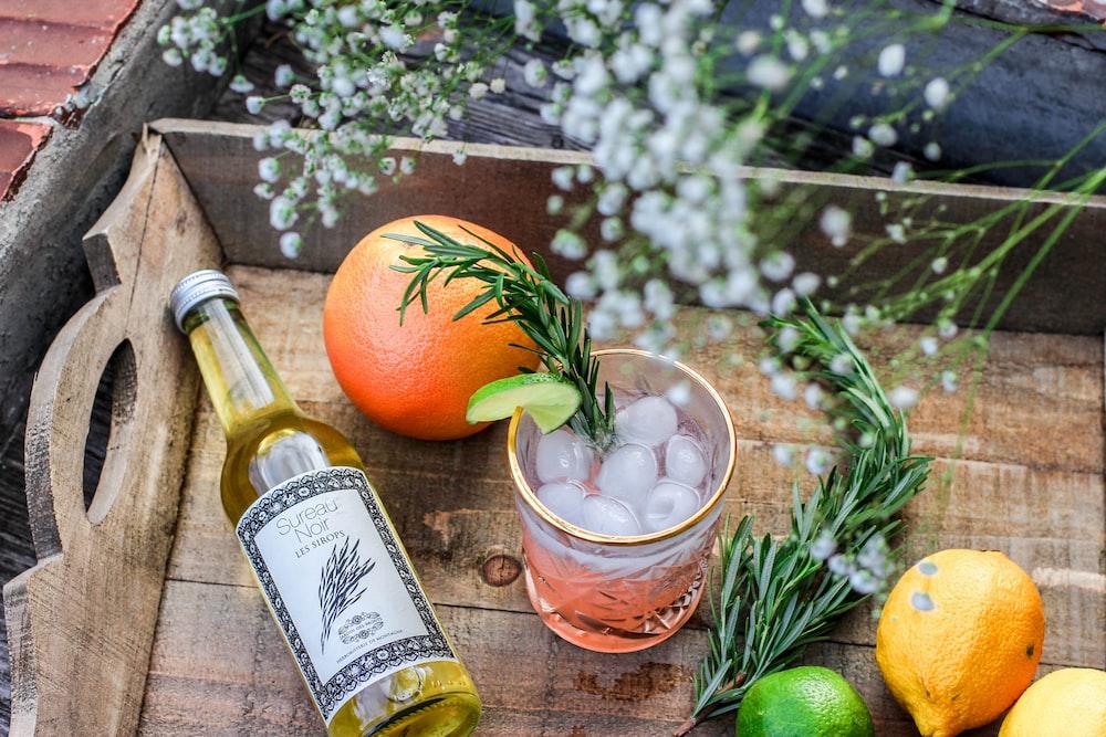 orange fruit beside bottle of drink