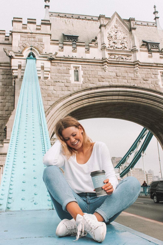 woman sitting on metal surface near London Tower Bridge during daytime