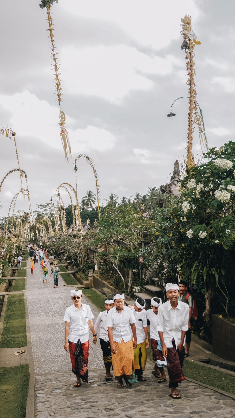 group of men walking at middle of walkway beside flowers