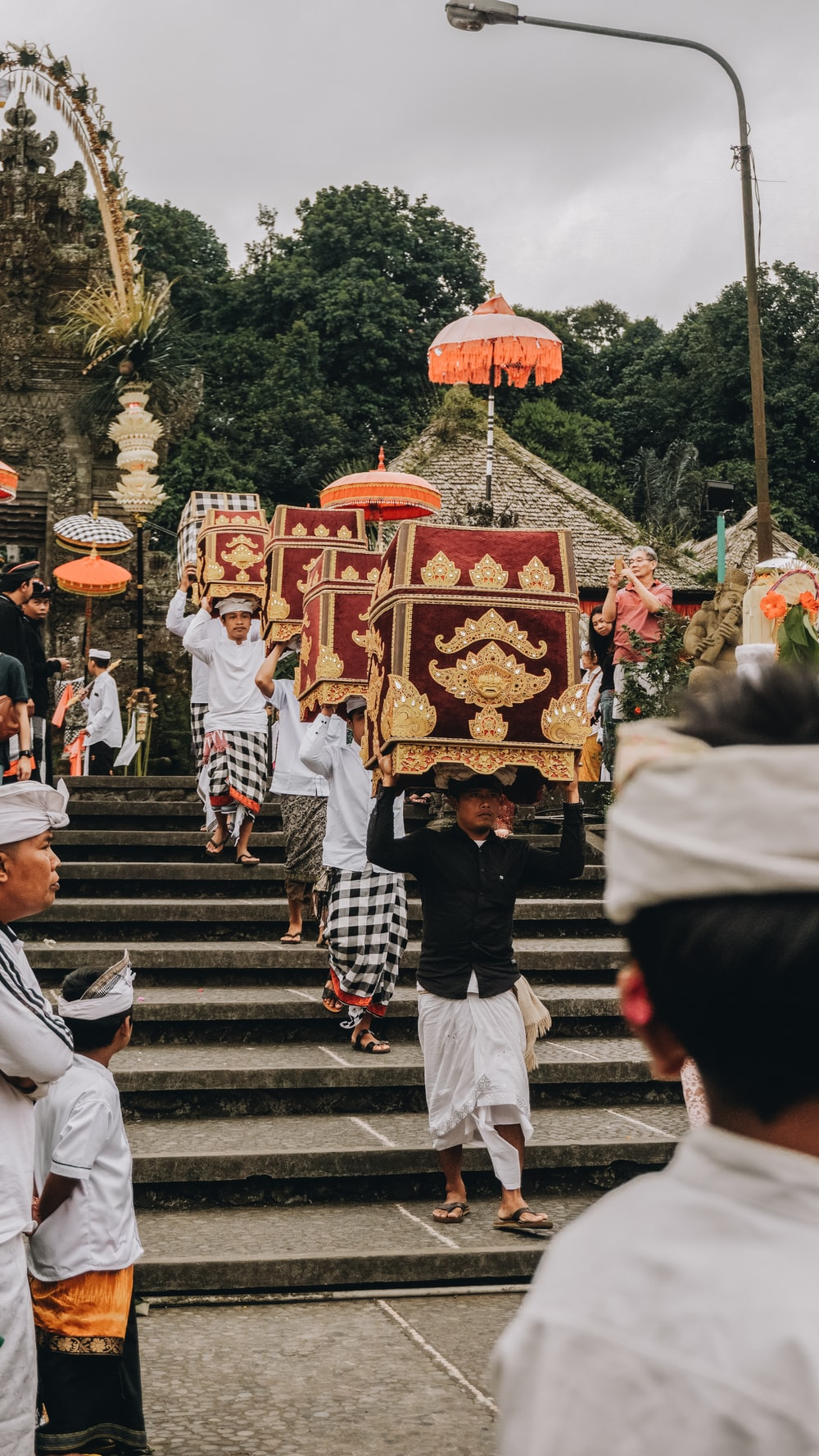 people walking down on stairs carrying altars