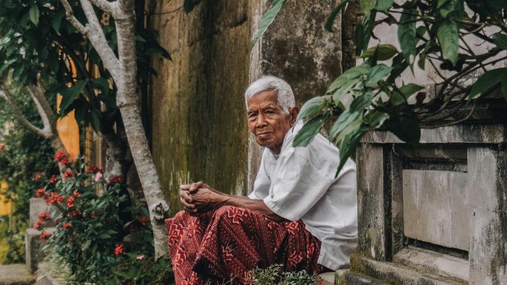 man siting beside wall near trees
