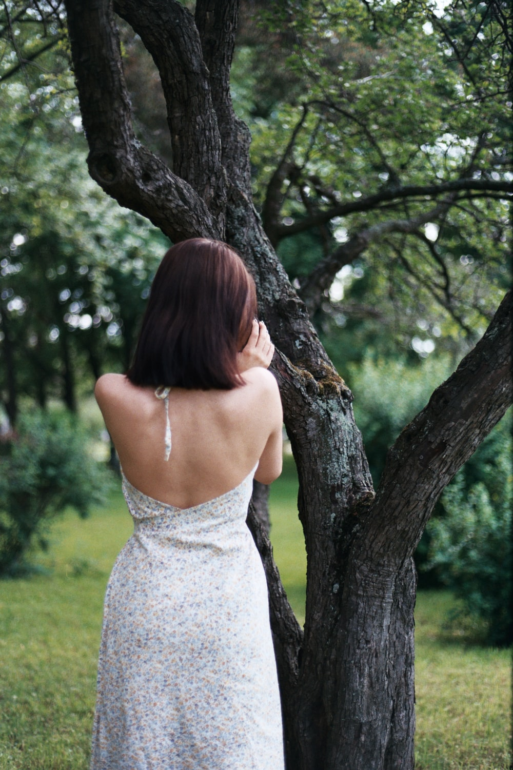 woman in white halter dress looking at tree