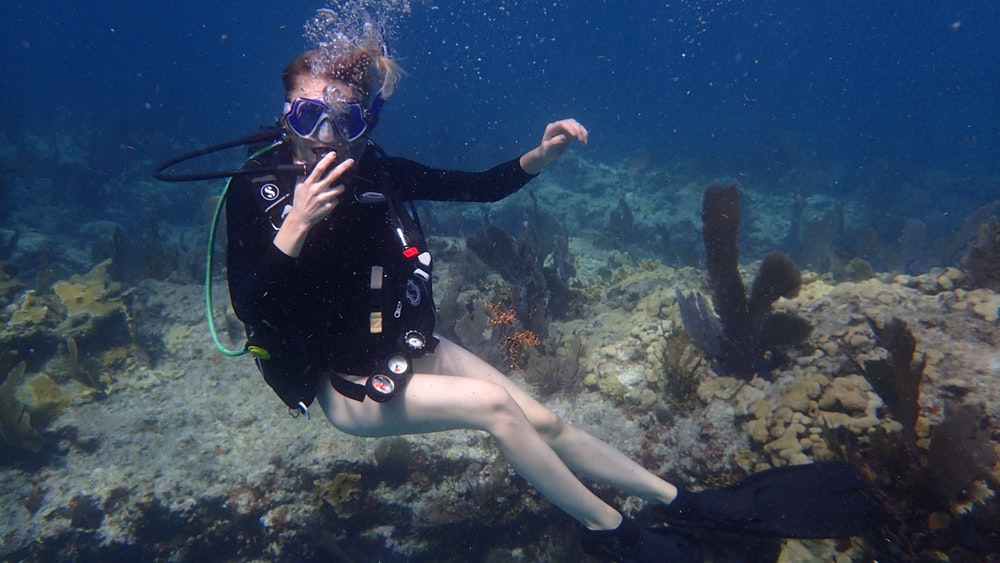 underwater photography of woman with oxygen tank and black flippers