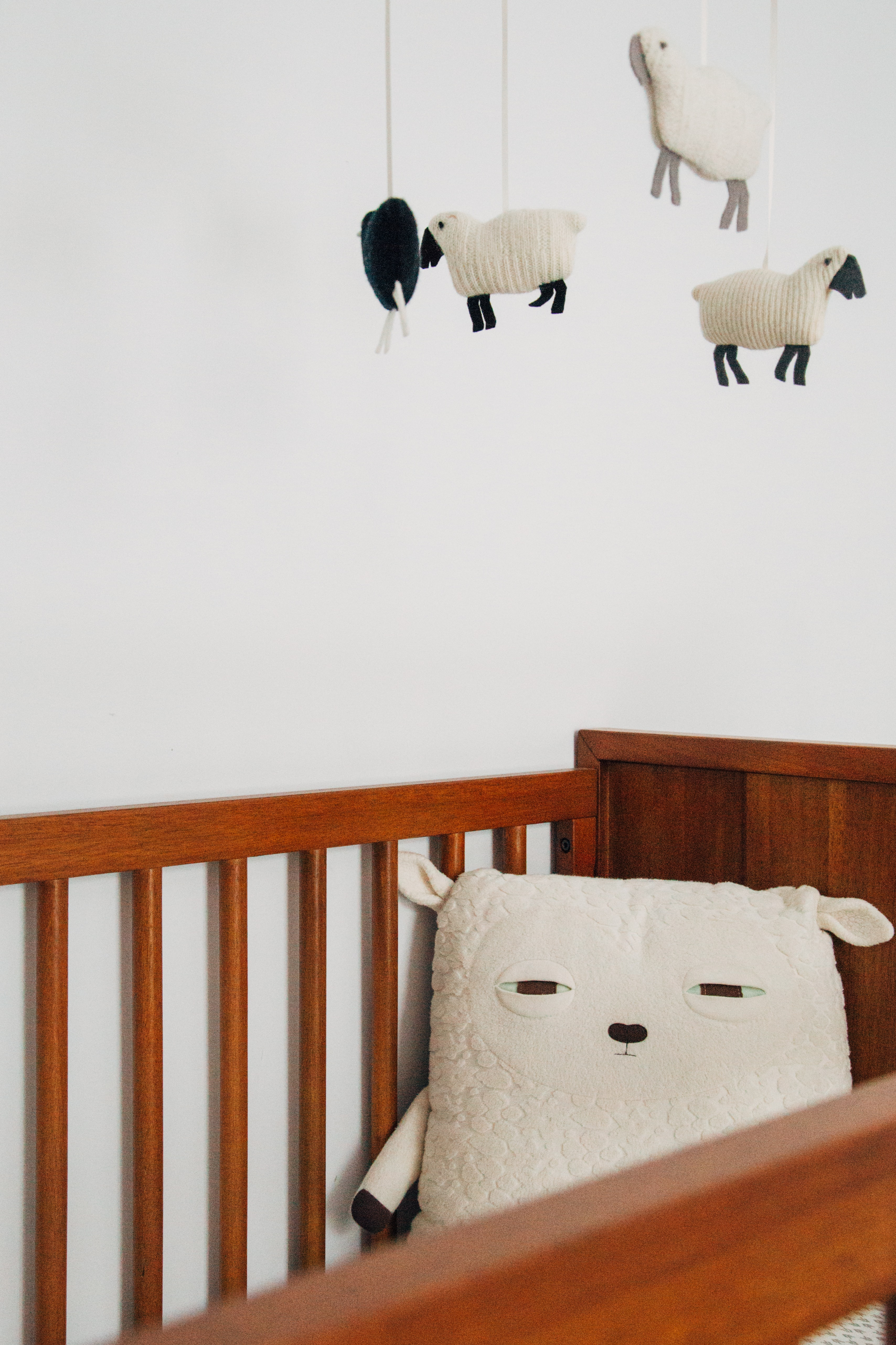 crib with sheep pillow and crib mobile