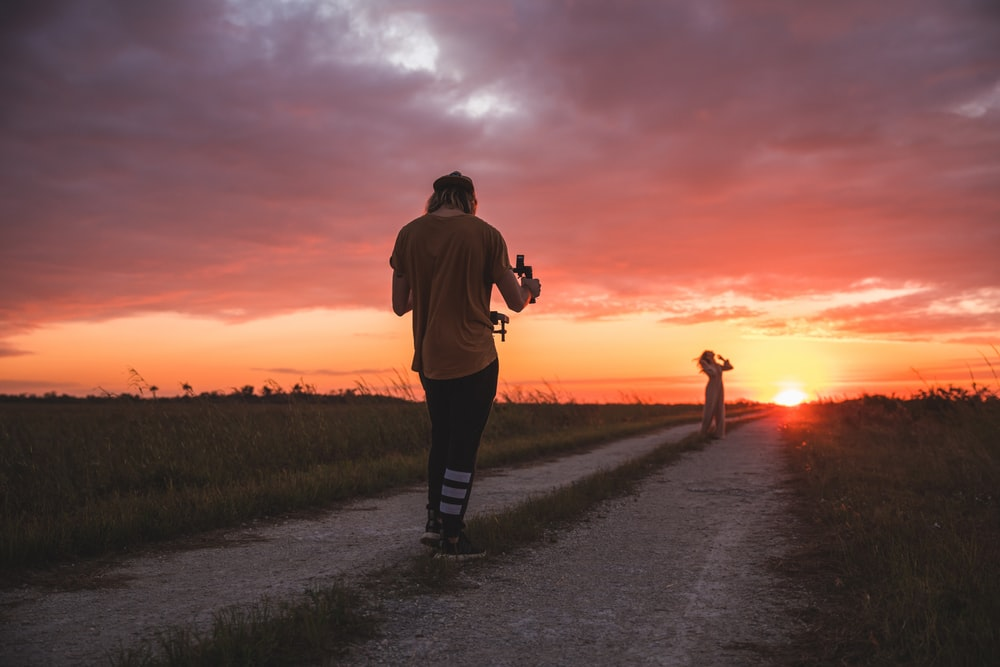 man taking photo of woman during golden hour
