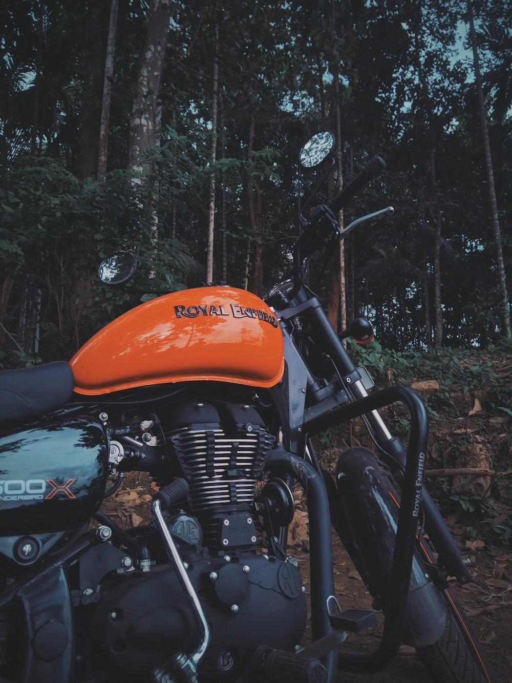 black and orange Royal Enfield motorcycle during daytime