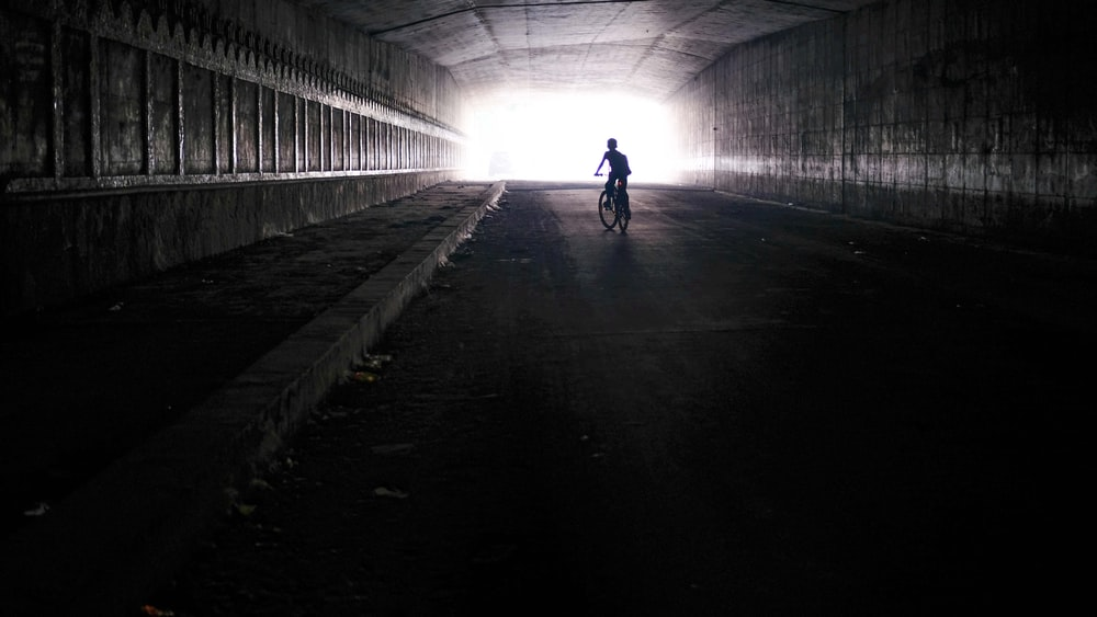 silhouette photography of person riding bicycle