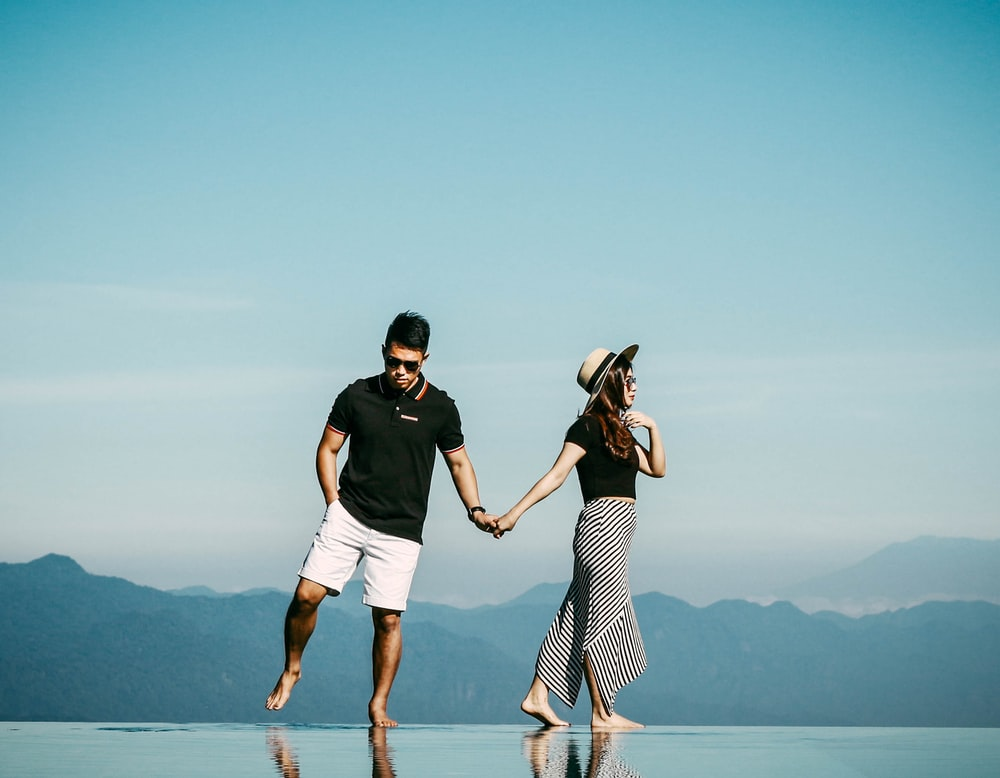 woman holding man's hand while walking