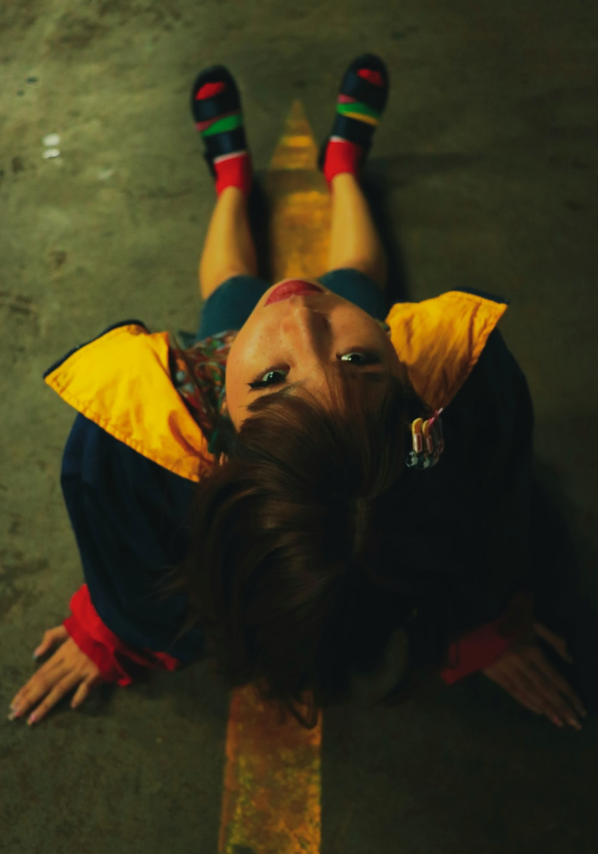 girl sitting on floor wearing yellow and black jacket