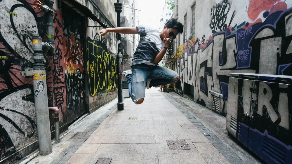 man wearing black t-shirt while jumping between concrete building