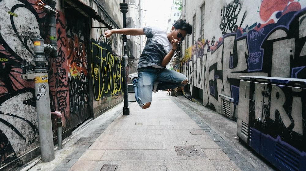 man wearing black t-shirt while jumping between concrete building