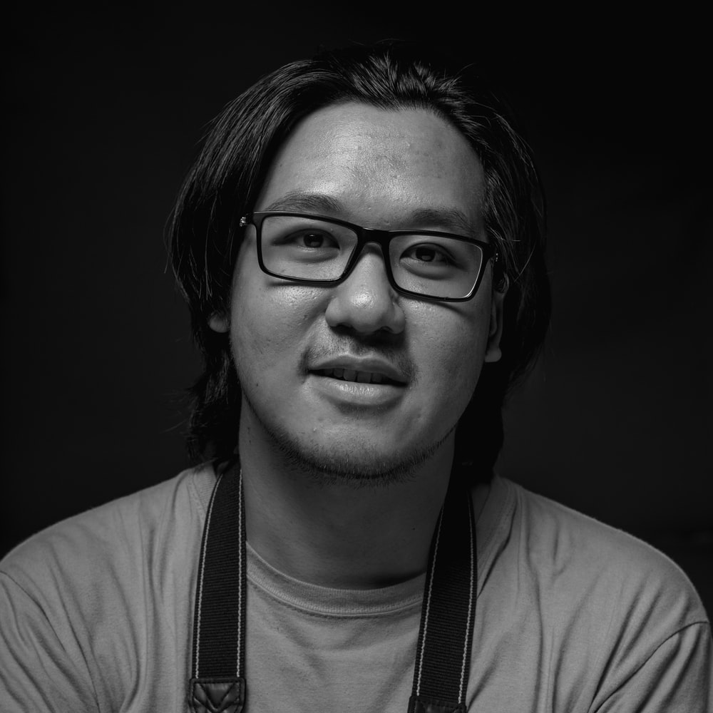 grayscale photography of man wearing eyeglasses and crew-neck shirt