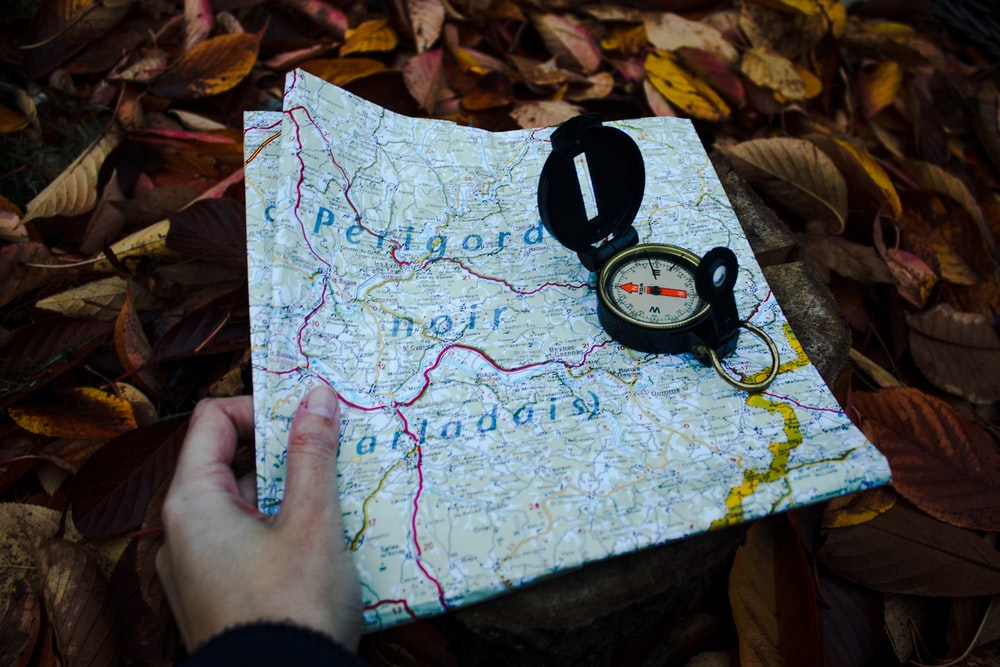 round black compass and white and blue map