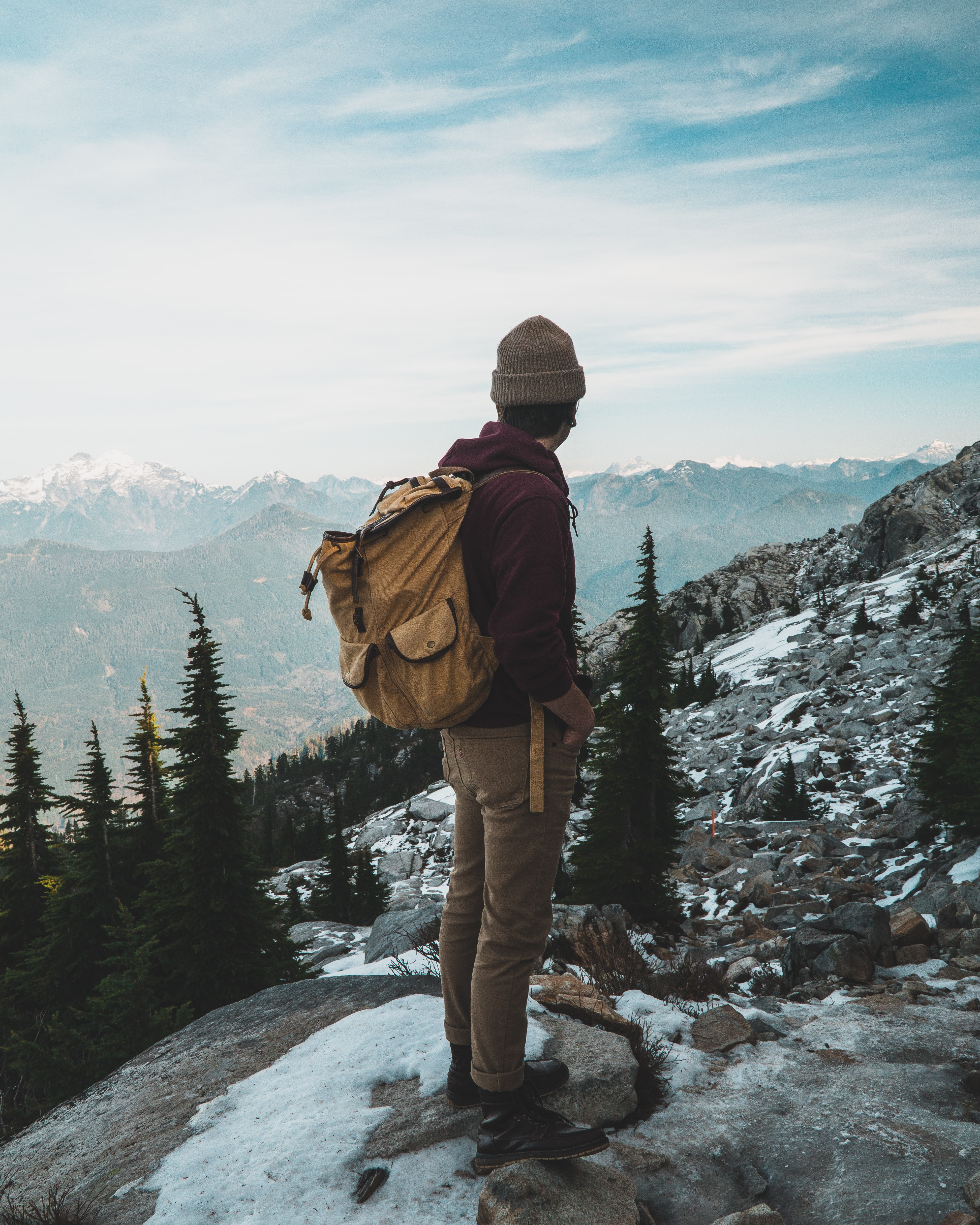 person wearing jacket and hiking backpack standing on cliff while watching mountain during daytime