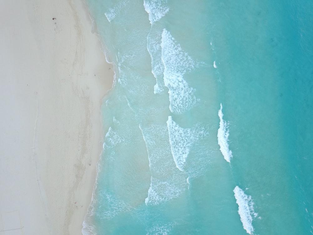 bird's-eye view photo of sea waves crashing on shore