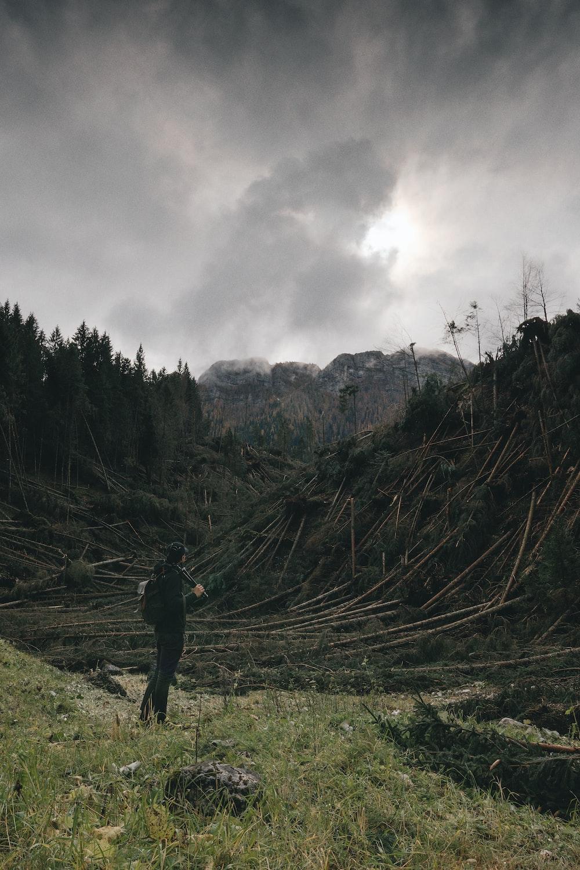 man standing on grass field facing mountain