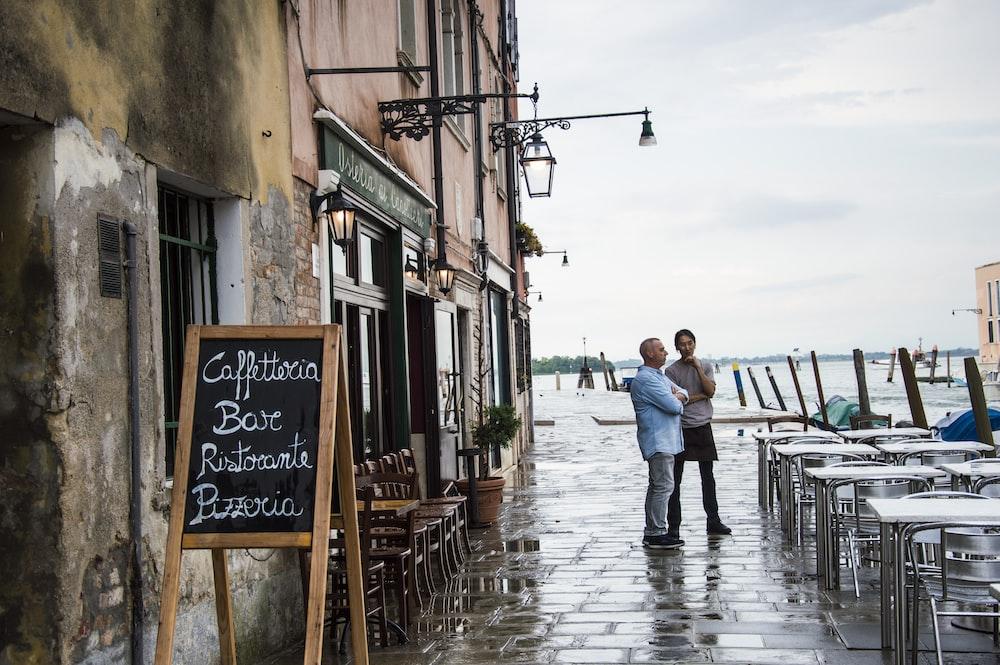 couple men standing outside near table