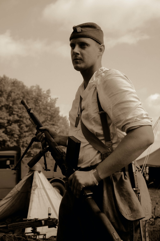 sepia photography of man holding riffle