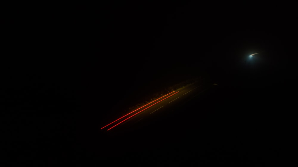 time-lapse photography of moving vehicle on road at night