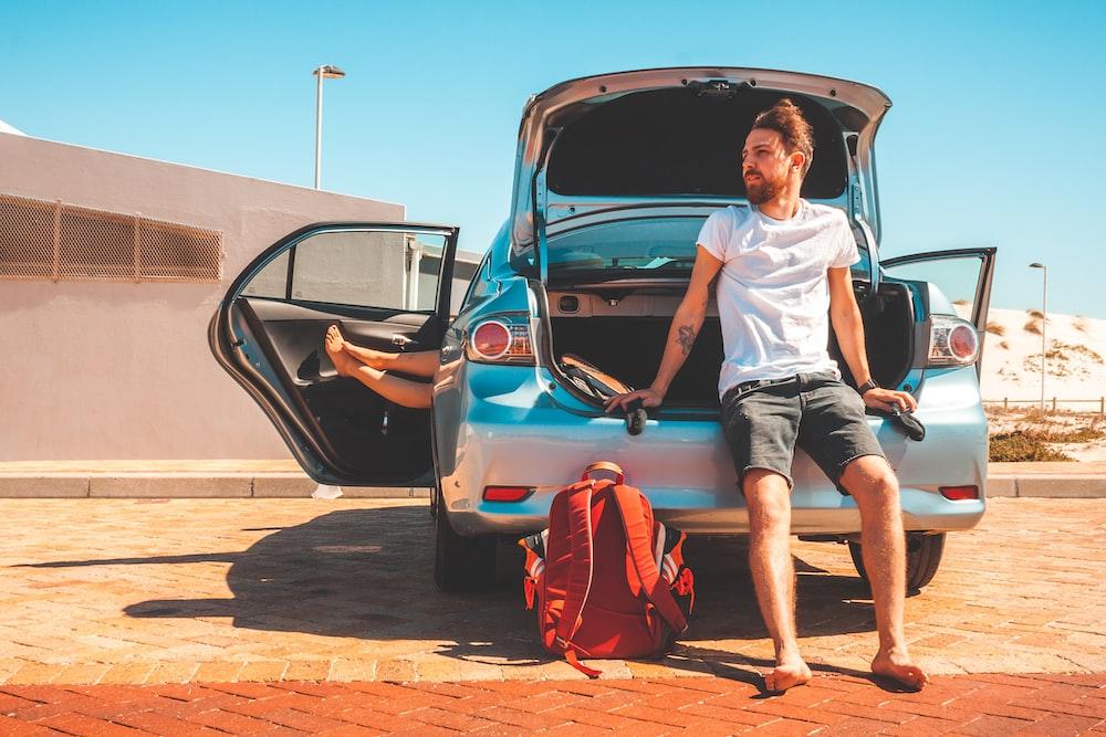 man sitting on car rear bumper