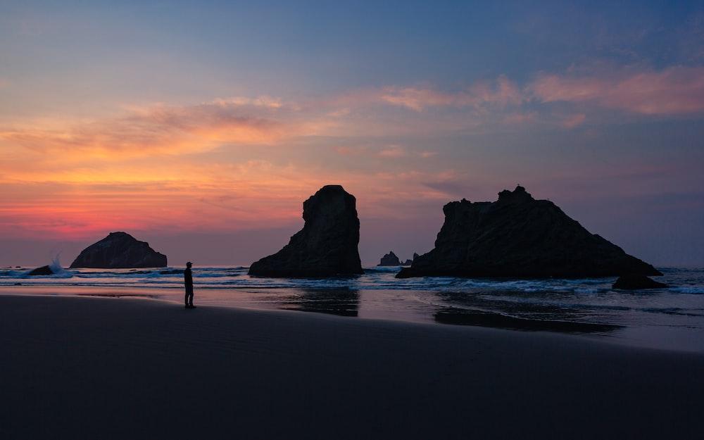 silhouette of man standing on shoreline
