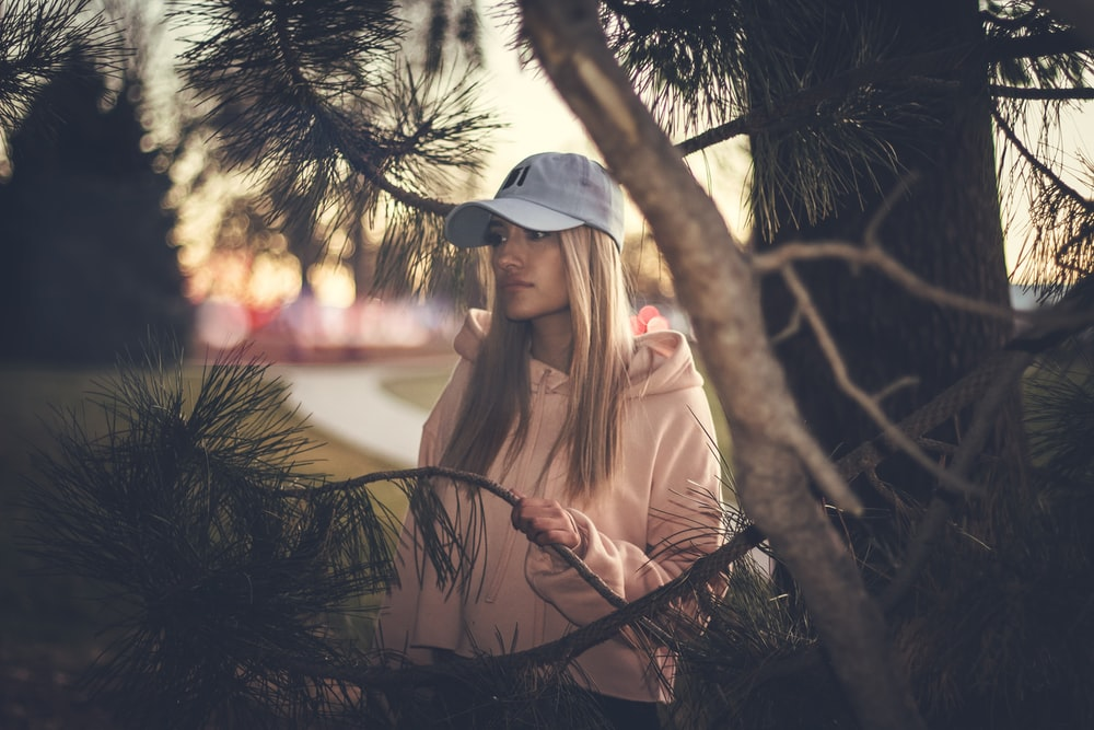 woman wearing white cap and pink hoodie