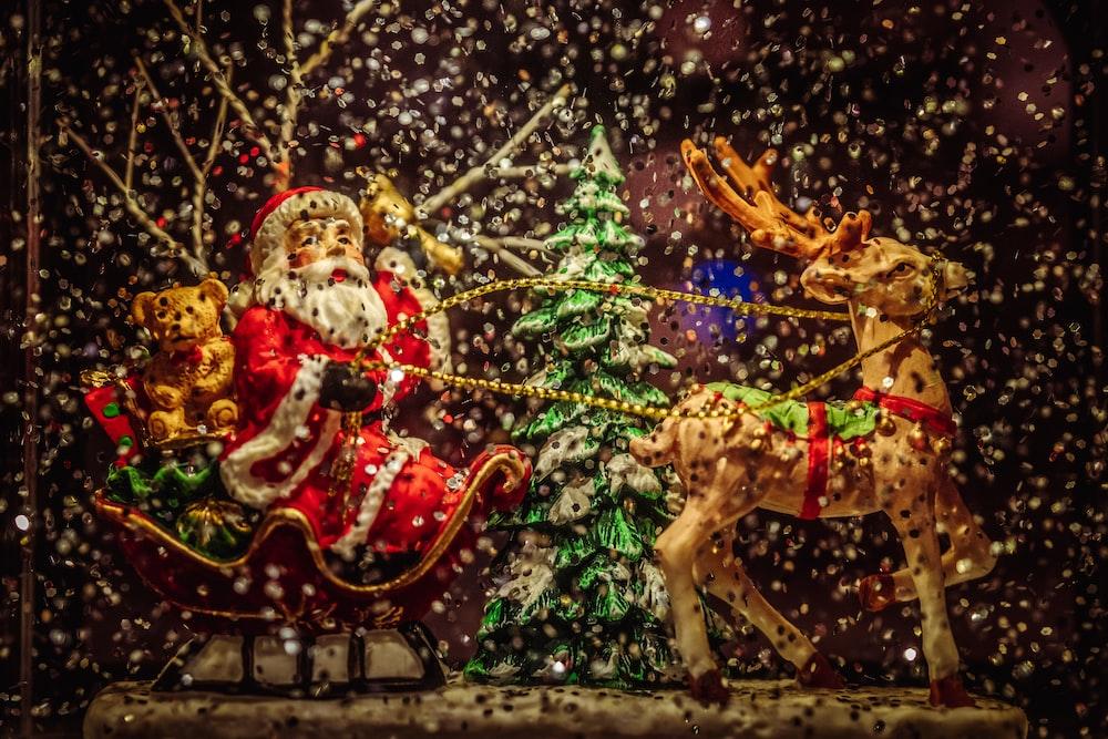 Santa Claus riding sleigh holding rope of reindeer figurine