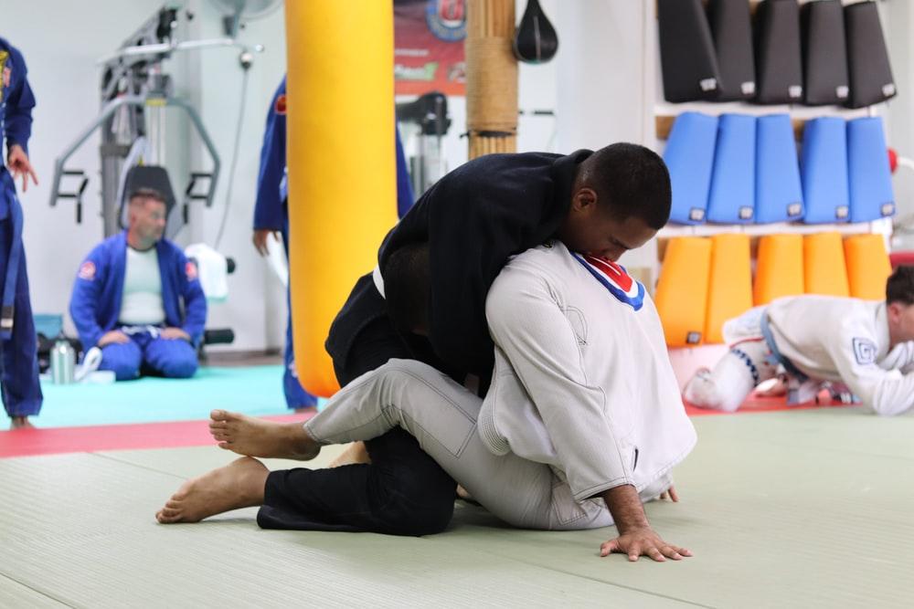 two men perform Brazilian jiu-jitsu