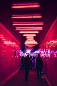 two person walking along hallway
