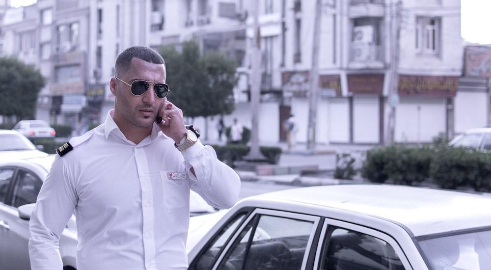 man wearing white dress shirt walking on street