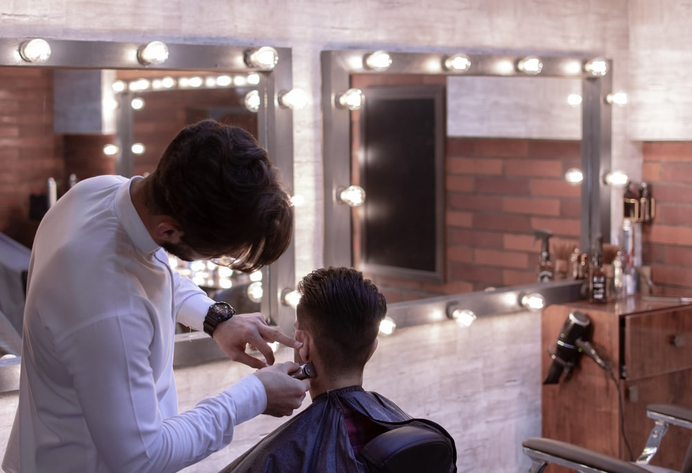 barber shaves man's hair at the barber shop