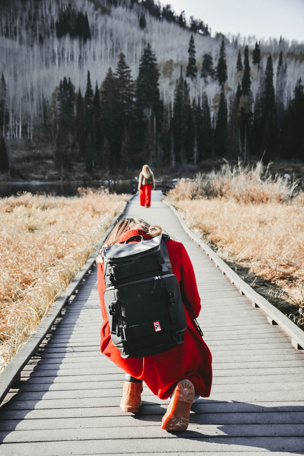 person wearing red cloth and black bag sitting on bridge in front of forest