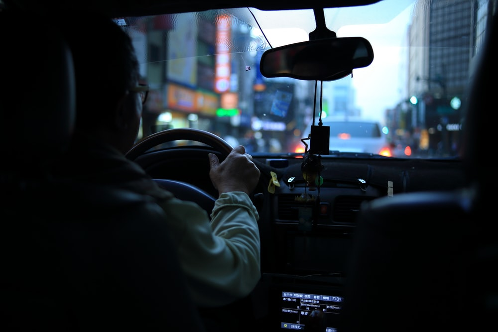 man driving car with bokeh lights