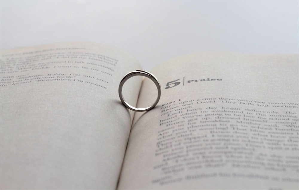 silver-colored ring on opened book
