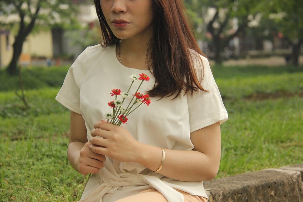 woman sitting on grey bench holding flower