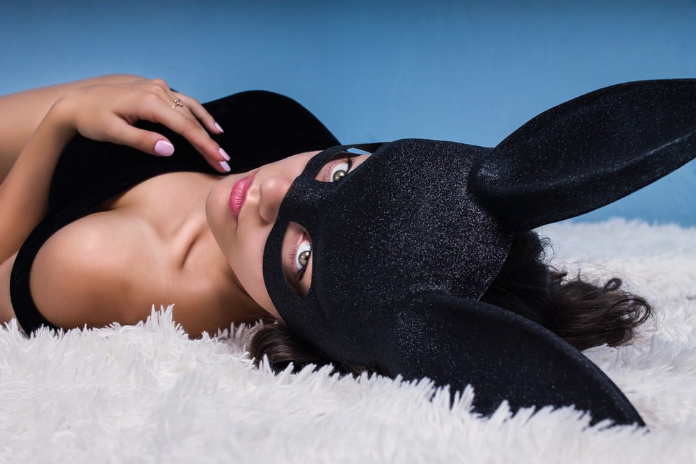 woman wearing black cat mask while lying down