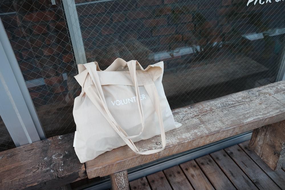 beige tote bag on bench