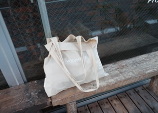 beige tote bag on bench