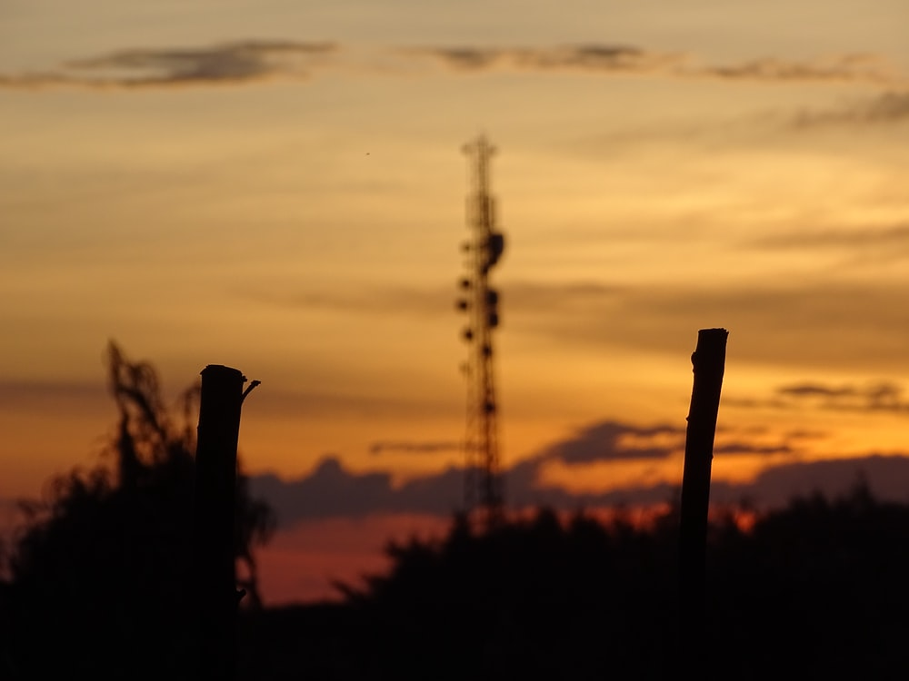 silhouette photography of stick near electric tower