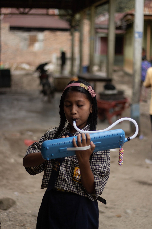 girl playing blue musical equipment