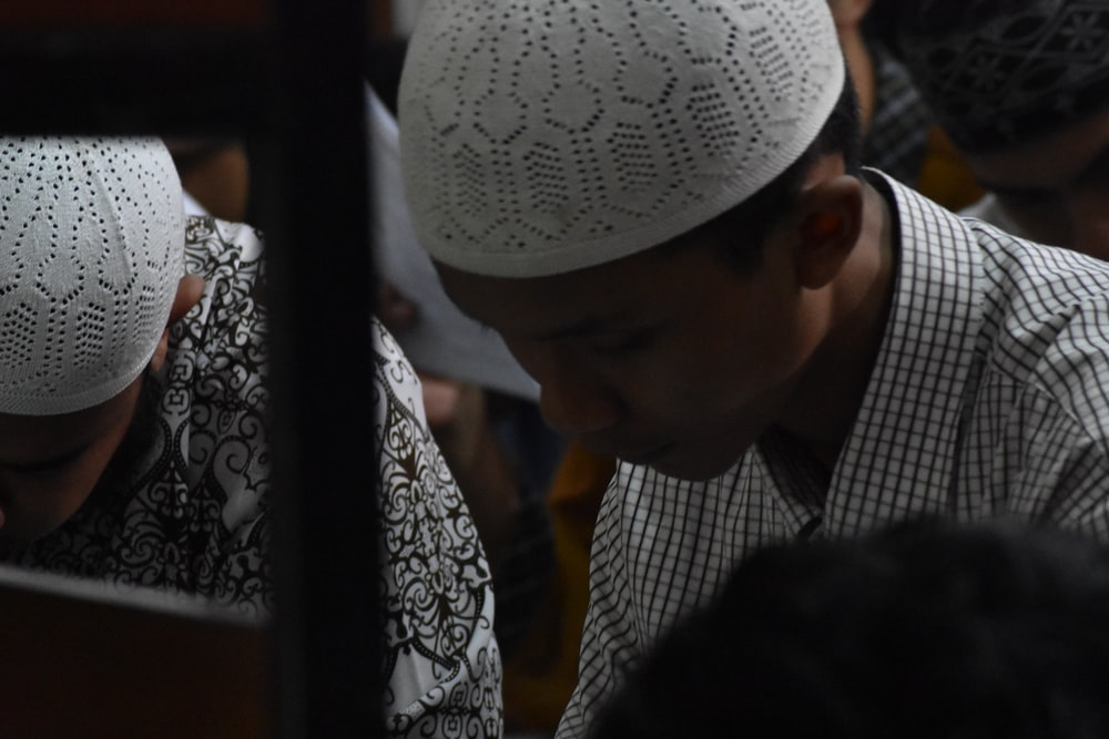 selective focus photo of man wearing taqiyah cap