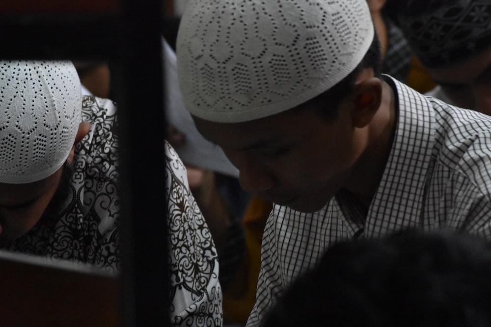 selective focus photo of man wearing taqiyah cap
